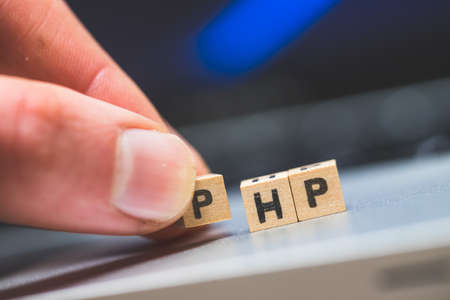 """Wooden cubes with the letters """"PHP"""" are lying on a laptop"""
