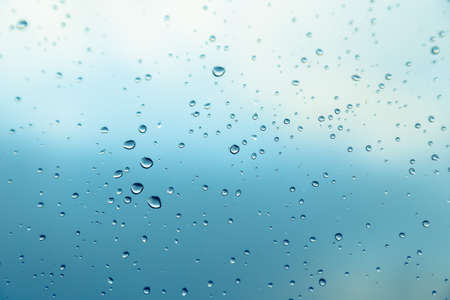 Close up picture of water drops on the window. Blue sky and clouds in the background.