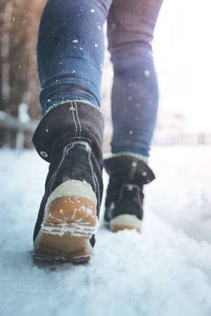 Girl in blue jeans is hiking in the wintertime, legs and shoes Standard-Bild