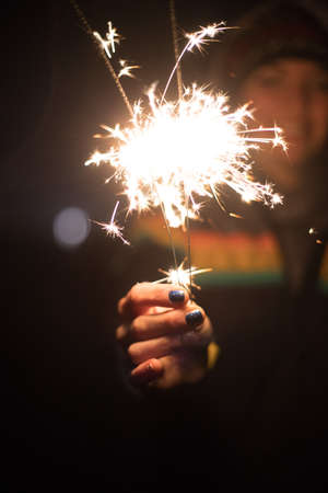 Smiling girl is holding a sparkler in her hand, new year, outdoors Banque d'images