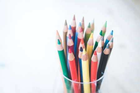 Colored pencils in a can on rustic wooden table, white background Standard-Bild