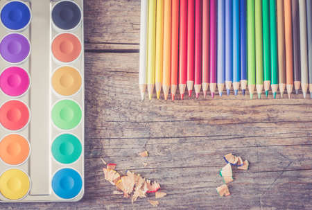 Set of multi-colored pencils, water colors and brushes on a rustically wooden table, copy space