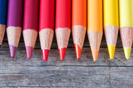 Set of multi-colored pencils on a rustically wooden table, copy space