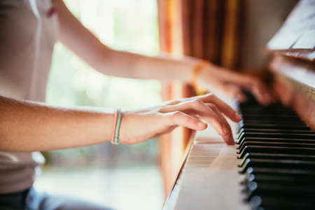 Young girl is practicing piano at home. Clipping of piano and hands.