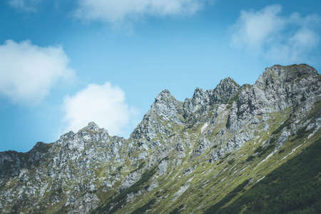 Picture of rugged mountains in the alps, blue sky with clouds