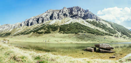 Lake with clear water in the foreground, rugged mountains in the background Standard-Bild