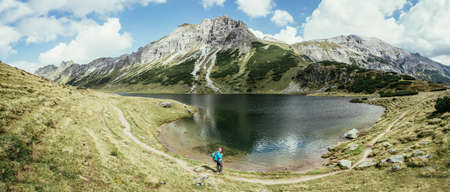 Mountain landscape: Rocky mountain range, clear water lake and blue cloudy sky; panorama