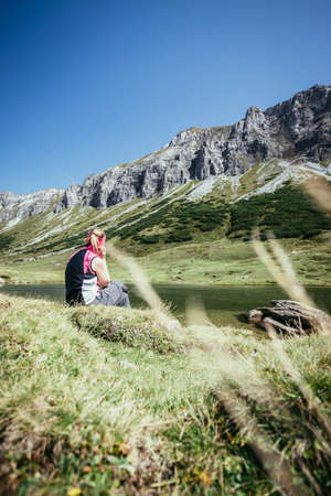 Woman in sportswear is doing a break during a hike: sitting on the ground and enjoying the view over the mountains and a lake