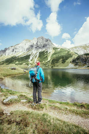 Female blonde mountain climber with backpack is enjoying the view Standard-Bild