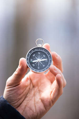 Man on an adventure is holding a compass in his hand for finding is route