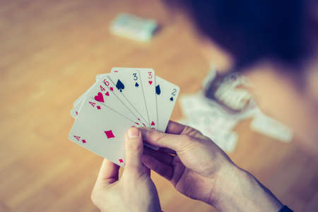 Young man is playing cards, cutout of his hands