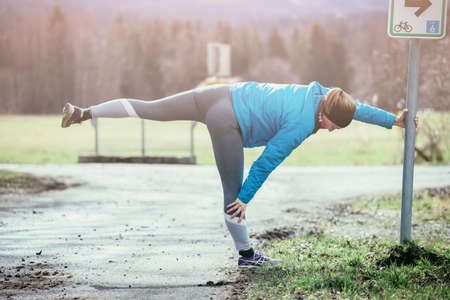 Young woman is bending and stretching before going to run Standard-Bild