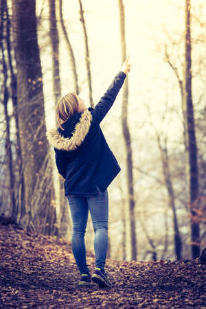 Girl is taking a walk in the wood, autumn time