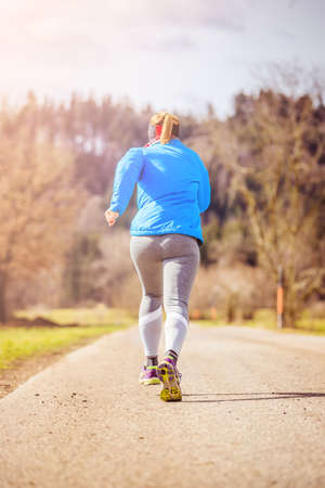 Young woman is jogging in the countryside