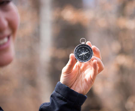 Girl on an adventure is holding a compass in her hand for finding is route, blurry face Standard-Bild