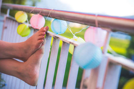 Relaxation / holidays on the terrace: Feet and colorful lampions