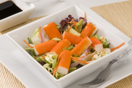 Surimi salad in a white square plate. Selective focus.  Stock Photo