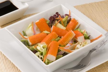 Surimi Salat in einer wei�en quadratischen Platte. Selektiver Fokus.