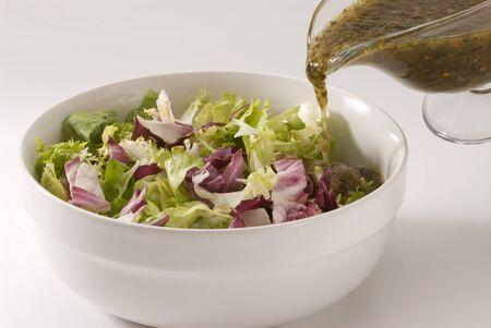 Vinaigrette Gie�en �ber frischen Salat Sch�ssel. Lizenzfreie Bilder