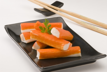 Surimi or crab sticks in a black ceramic plate. Selective focus. White background. Stock Photo