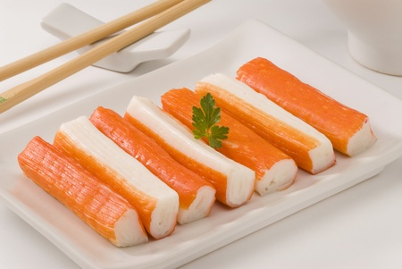 Surimi or crab sticks in a white plate. Selective focus. White background. Stock Photo