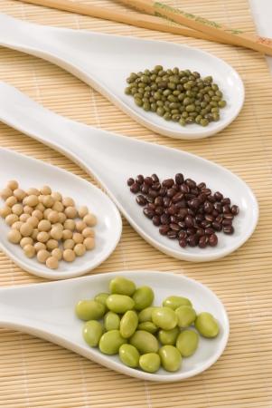 legumbres secas: Surtido de soja secos y frescos en cucharas blancas Foto de archivo