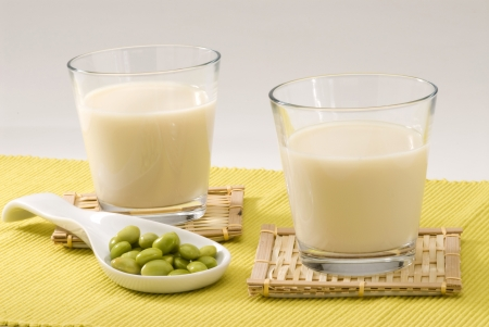 Soy milk in a glass  Fresh soy beans in foreground  White background