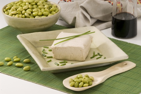 Tofu on a ceramic plate  Fresh soy beans on foreground
