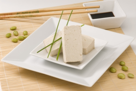Tofu on a white plate  Fresh soy beans on foreground
