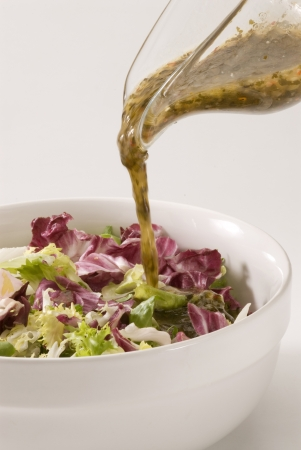 Vinaigrette dressing pouring over fresh salad bowl