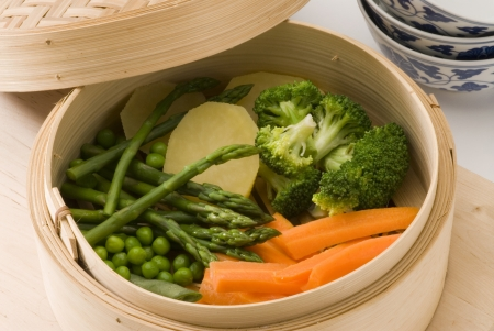 Assorted steamed vegetables in a bamboo steamer  Selective focus  Stock Photo