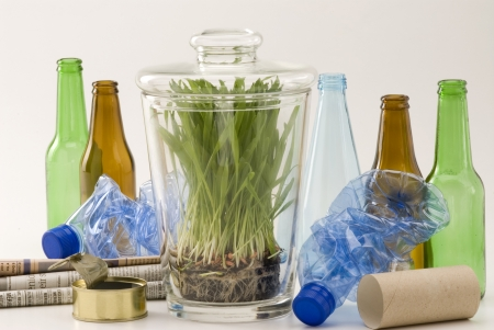 waste products: Grass growing in glass jar among household recycling items  White background