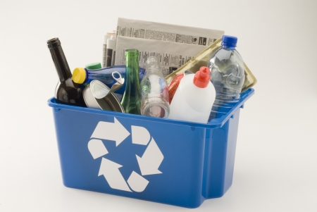 Blue recycling bin full of household materials including metal plastic glass paper and cardboard  White background   Stock Photo