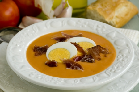 andalusian cuisine: Spanish Cuisine  Salmorejo  Andalusian cold soup in a white plate, served with boiled egg and serrano ham  Selective focus  Stock Photo