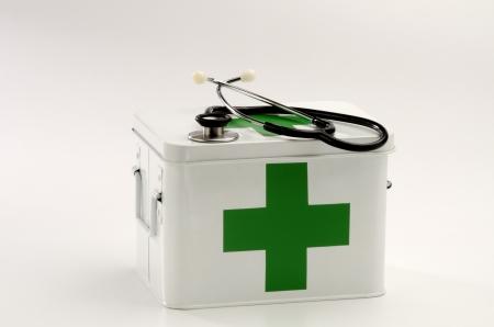 first aid box: Caja de primeros auxilios y un estetoscopio en el fondo blanco Foto de archivo