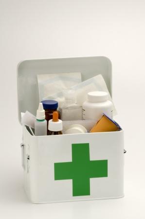 primeros auxilios: Kit de primeros auxilios abierto lleno de suministros médicos en el fondo blanco Foto de archivo