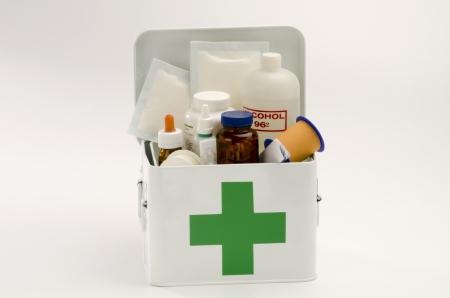 primeros auxilios: Kit de primeros auxilios abierto lleno de suministros m�dicos en el fondo blanco Foto de archivo