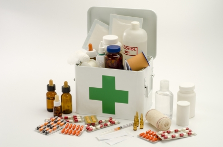 botiquin primeros auxilios: Kit de primeros auxilios abierto lleno de suministros m�dicos en el fondo blanco Foto de archivo