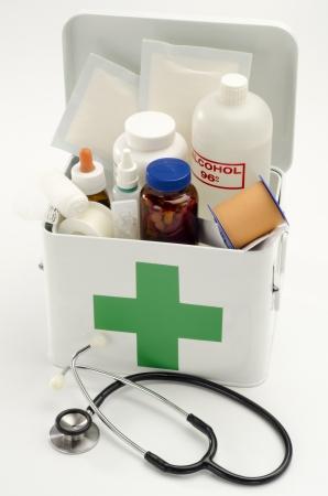 first aid kit: Kit de primeros auxilios abierto lleno de suministros m�dicos en el fondo blanco Foto de archivo