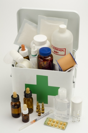 Open first aid kit filled with medical supplies in white background photo
