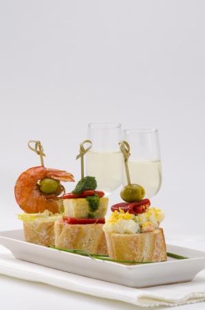 Spanische K�che. Montaditos. Geschnitten Brot garniert mit einer Vielzahl von Vorspeisen. Spanisch Tapas.Two Gl�ser Sherry Wein in den Hintergrund.