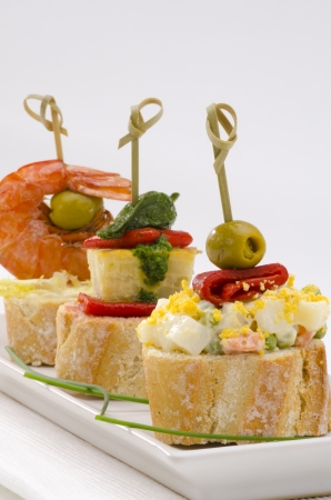 spanish tapas: Spanish cuisine. Montaditos. Sliced bread topped with a variety of appetizers. Spanish Tapas. Focus on foreground. Stock Photo