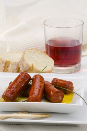 tapas espa�olas: Tapas espa�olas. Salchicha picante servido en un plato blanco. Chistorra. Enfoque en primer plano.