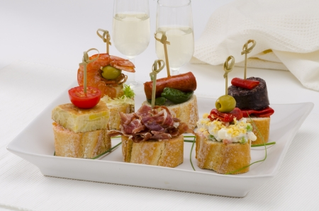 Spanish cuisine  Montaditos  Sliced bread topped with a variety of appetizers  Spanish Tapas Two glasses of Sherry wine in the background  photo