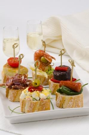 tapas espa�olas: Pan Montaditos cocina espa�ola en rodajas cubierta con una gran variedad de aperitivos Tapas espa�olas Dos vasos de vino de Jerez en el fondo