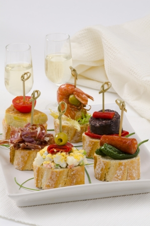 spanish tapas: Spanish cuisine  Montaditos  Sliced bread topped with a variety of appetizers  Spanish Tapas Two glasses of Sherry wine in the background