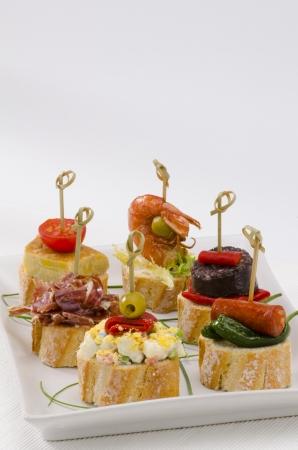 tapas espa�olas: Montaditos cocina espa�ola rebanada de pan cubierto con una variedad de aperitivos tapas espa�olas Foto de archivo
