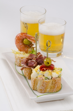 spanish tapas: Spanish cuisine  Montaditos  Sliced bread topped with a variety of appetizers  Spanish Tapas  Two glasses of beer in the background