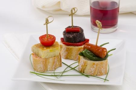 tapas espa�olas: Montaditos cocina espa�ola pan rebanado rematado con una gran variedad de aperitivos Tapas espa�olas Un vaso de vino tinto en el fondo