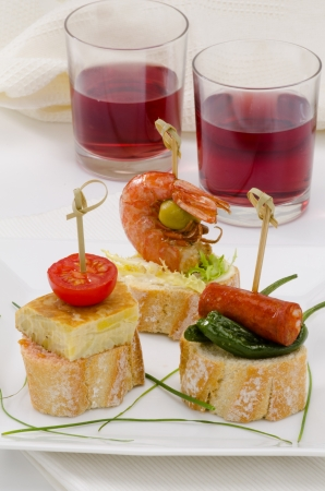 Spanish cuisine  Montaditos  Sliced bread topped with a variety of appetizers  Spanish Tapas Two glasses of red wine in the background  photo